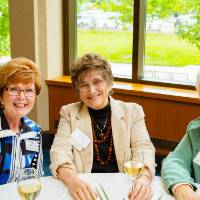 Three guests sitting at a table at the Retiree Reception.
